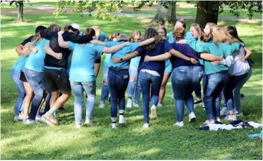Sisters of Delta Omicron Pi huddle and chant during the make up Running of the Bulls event.